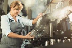 Erfaret baristadanandekaffe i yrkesmässig kaffemaskin royaltyfria bilder