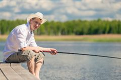 Erfaret fiskaresammanträde på en träpir och fiske arkivfoton