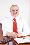 Erfaret kontorsframstickande vid skrivbordet arkivbilder