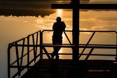 Erfaret manfiske på solnedgången på kusten av den fridsamma sjön royaltyfri fotografi