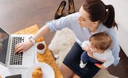 Erfinderische zeitgenössische Mutter, die morgens mehrere Dinge gleichzeitig tut Lizenzfreie Stockfotos