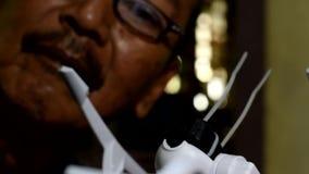 Erfinderischer, alter Mann reich an Hilfsquellen, der gebrochenen Viererkabelhubschrauber kontrolliert stock video
