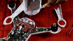 Erfinderischer, alter Mann reich an Hilfsquellen, der gebrochenen Viererkabelhubschrauber repariert stock video