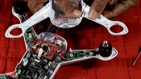 Erfinderischer, alter Mann reich an Hilfsquellen, der gebrochenen Viererkabelhubschrauber repariert stock video footage