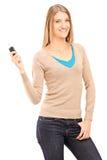 Erfüllte junge Frau, die einen Autoschlüssel hält Stockfotos