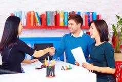 Erfüllte Kunden, Paare nach erfolgreichen Geschäftsverhandlungen im Büro Lizenzfreies Stockbild
