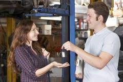 Erfüllter Kunde, der Auto vom Garagen-Mechaniker sammelt Stockbild