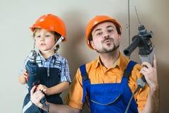 Erfüllter Vati mit seinem Sohn, der Reparaturen tut Stockbilder