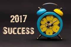 Erfolg 2017 geschrieben mit Wecker auf schwarzen Papierhintergrund Lizenzfreie Stockfotos
