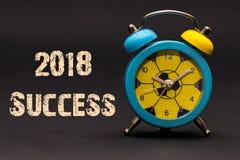 Erfolg 2018 geschrieben mit Wecker auf schwarzen Papierhintergrund Lizenzfreies Stockbild