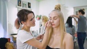 Erfolgreich, Multischönheitssalon Arbeit einiger Fachleute mit ihren Kunden Im Rahmen einer attraktiven blonden Frau stock video footage