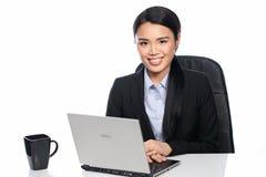 Erfolgreiche asiatische Geschäftsfrau an ihrem Schreibtisch lizenzfreie stockfotografie