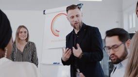 Erfolgreiche Berufsmitte alterte den Chefgeschäftsmann, der Verkäufe zum Team im modernen Büro, Zeitlupe ROTES EPOS erklärt stock video