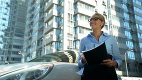 Erfolgreiche businesslady haltene Papiere in den Händen, lächelnd, neue Büros betrachtend lizenzfreies stockbild