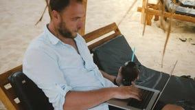 Erfolgreiche ernste Mitte alterte den Geschäftsmann, der im Klubsessel auf dem Strand mit Fruchtgetränk und dem Laptopdenken sitz stock video footage