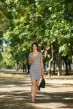 Erfolgreiche Frau im Park Hübsches Mädchen mit einem Cocktail auf einem natürlichen Hintergrund Gehen außerhalb des Konzeptes Kop Stockfotos
