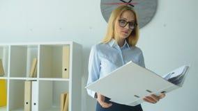Erfolgreiche Geschäftsdame, die durch Dokument schaut stock video footage