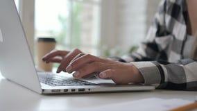 Erfolgreiche Geschäftseigentümergeschäftsfrau, die auf dem Laptop, bei Tisch arbeitend im Innenministerium schreibt stock video