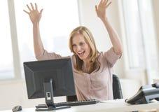 Erfolgreiche Geschäftsfrau With Arms Raised, das Computer betrachtet Stockfotografie