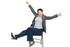 Erfolgreiche Geschäftsfrau auf Stuhl gibt Daumen Stockfoto