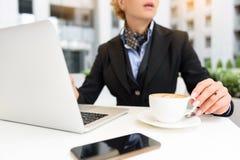 Erfolgreiche Geschäftsfrau, die an Computer im Café arbeitet Lizenzfreies Stockfoto