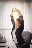 Erfolgreiche Geschäftsfrau, die in ihrem Stuhl im Büro sich entspannt stockbilder
