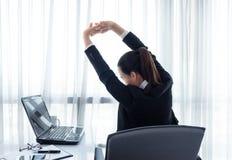 Erfolgreiche Geschäftsfrau, die in ihrem Stuhl im Büro sich entspannt stockfoto