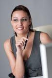 Erfolgreiche Geschäftsfrau, die im Büro denkt Lizenzfreie Stockfotos