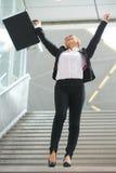 Erfolgreiche Geschäftsfrau, die mit den Armen angehoben feiert Stockbild