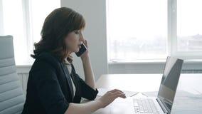 Erfolgreiche Geschäftsfrau, die am Telefon, bei Tisch arbeitend mit Laptop im Büro spricht stock video