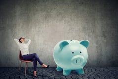 Erfolgreiche Geschäftsfrau mit dem Entspannungsc$sitzen des großen Sparschweins auf Stuhl stockfotos