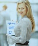 Erfolgreiche Geschäftsfrau mit einem Finanzdiagramm auf einer Tablette auf dem Hintergrund des Geschäftsteams im Büro Lizenzfreie Stockfotos
