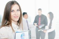Erfolgreiche Geschäftsfrau am Vordergrund und Geschäft team am Hintergrund Stockfotografie