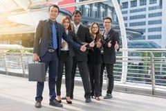 Erfolgreiche Geschäftsgruppe mit den Daumen oben an der Stadt Stockfotografie