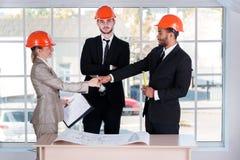 Erfolgreiche Geschäftsmannarchitekten, die Hände rütteln Stockfotografie
