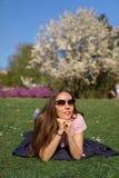 Erfolgreiche Gesch?ftsfrau, die auf dem Gras genie?t Freizeitfreizeit in einem Park mit bl?henden Kirschbl?te-Kirschb?umen liegt lizenzfreie stockfotografie