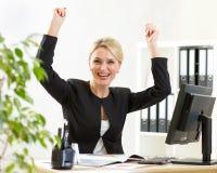 Erfolgreiche Geschäftsfrau von mittlerem Alter, welche die Arme oben sitzen am PC im Büro hält Lizenzfreie Stockfotos