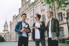 Erfolgreiche glückliche Studenten, die draußen nahen Campus oder Universität stehen stockfotos