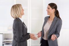 Erfolgreiche glückliche Geschäftsfrau zwei, die zusammen spricht Lizenzfreie Stockfotos