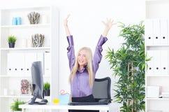 Erfolgreiche junge blonde Geschäftsfrau, Sieggeste, Hände oben, lächelnd im Büro Lizenzfreies Stockfoto