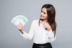 Erfolgreiche junge Frau, die auf den Euro lokalisiert auf weißem Hintergrund zeigt Lizenzfreies Stockfoto