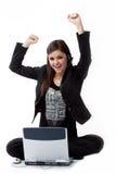Erfolgreiche junge Frau durch den Computer auf dem flo Stockbild