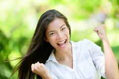Erfolgreiche junge Frau mit den geballten Fäusten im Park Stockfotos