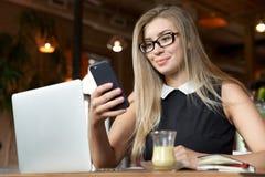 Erfolgreiche junge Geschäftsfrau, die auf einem Smartphone sitzt in einem Café mit einem Laptop und einer Tasse Tee oder Kaffee s lizenzfreie stockbilder