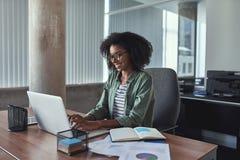 Erfolgreiche junge Geschäftsfrau, die Laptop verwendet lizenzfreies stockfoto