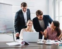 Erfolgreiche junge Geschäftsleute, die Laptop am Schreibtisch im Büro verwenden Stockfotos