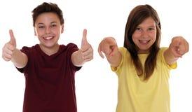 Erfolgreiche lächelnde Kinder, die sich Daumen zeigen Lizenzfreie Stockbilder