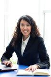 Erfolgreiche Geschäftsfrau am Büroarbeitsplatz mit Laptop u. Buch Stockbilder