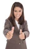 Erfolgreiche lokalisierte Geschäftsfrau im Braun mit den Daumen oben Stockfotografie