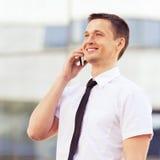 Erfolgreiche Männer, die um Handy ersuchen Stockbilder